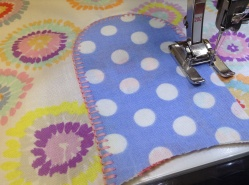 Machine embroidering the bib on to the dress