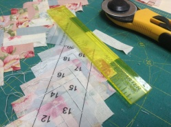 Trimming the seam allowance using a quarter inch ruler.