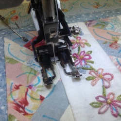 Quilting by stitching in the ditch using a walking foot.