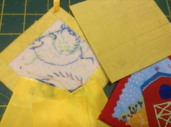 """Glued ribbon to the back of the rosette on right, background fabric glued onto 4"""" cardboard"""